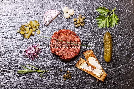 raw steak tartare on black slate