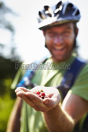 hiker on trail with native raspberries
