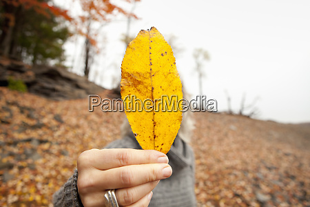 a woman holding out an autumn