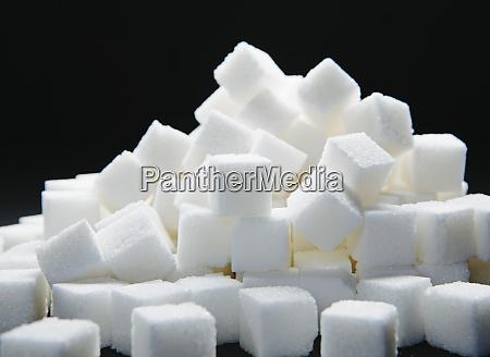 pile of sugar cubes black backdrop