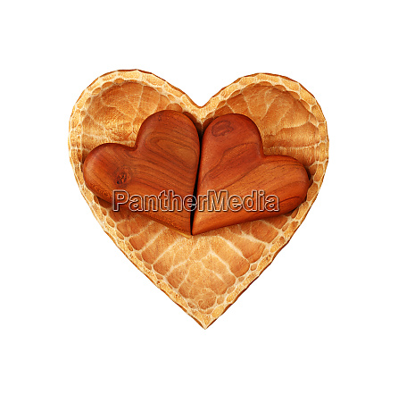 two brown wooden hearts in bowl