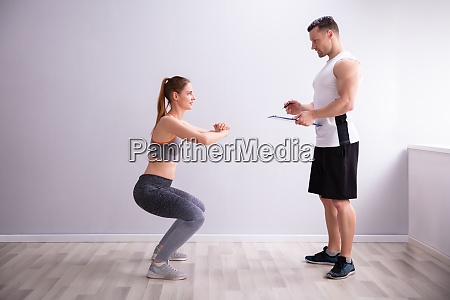 sporty woman doing deep squat exercise