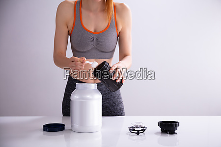 sporty woman making protein shake on