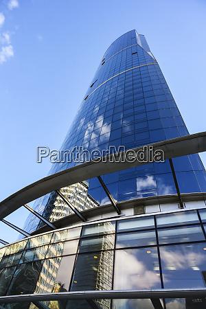 skyscraper with glass facade reflecting blue