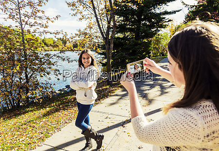 a girl photographing her sister during