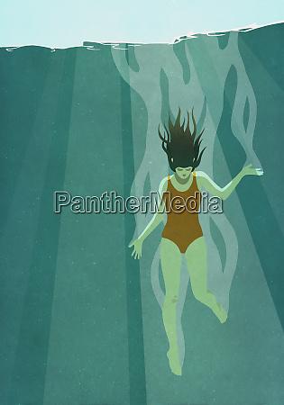woman swimming underwater in ocean