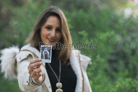 portrait woman showing instant photograph