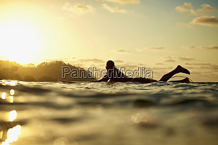male surfer laying on surfboard on