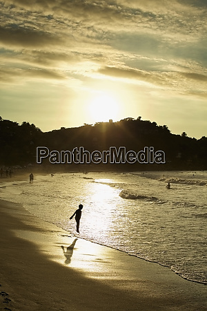 silhouette boy wading in ocean surf