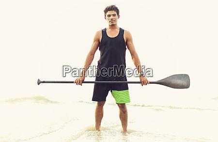 portrait confident young man holding oar