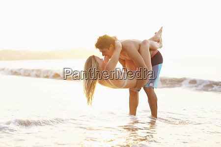 playful affectionate young couple wading in