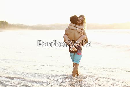 boyfriend carrying girlfriend in ocean surf