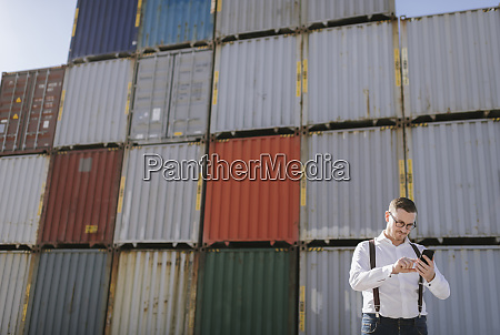 manager in front of cargo containers