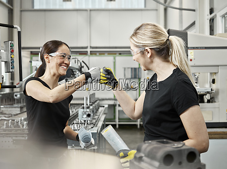 two woman at work fist bump