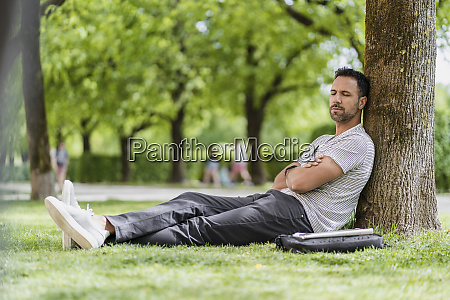 man leaning against a tree in