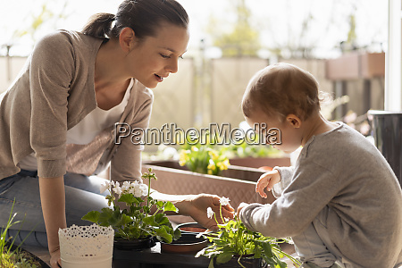mother and daughter planting flowers together