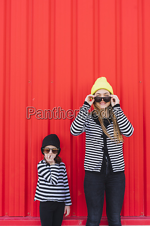 two fashionable sisters wearing caps and