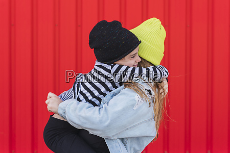 happy little girl hugging older sister