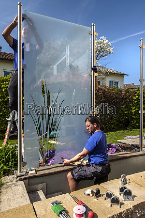germany glaziers attaching glass pane