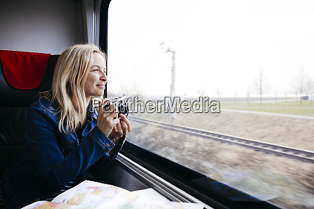 happy blond woman with camera travelling