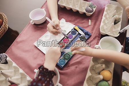 children painting easter eggs on table