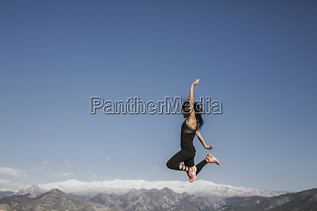 woman jumping with sierra nevada background