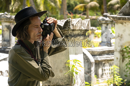 seychelles la digue man photographing gravestones
