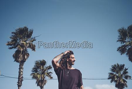 man posing among palm trees