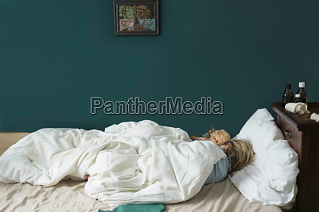 sick girl lying in bed with