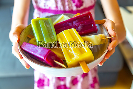 girl holding bowl with colorful popsicles