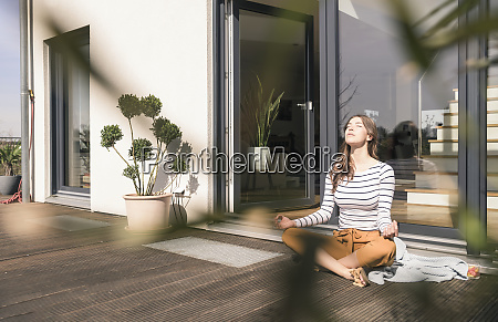 young woman sitting on terrace at