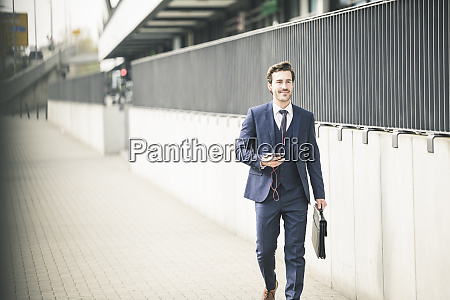 businessman walking in the city with