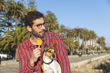 young man with dog eating ice