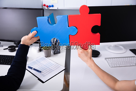 two businesspeoples hand holding jigsaw puzzle