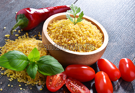 bowl of uncooked bulgur on wooden