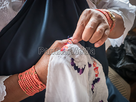 indigenous woman doing traditional embroidery otavalo