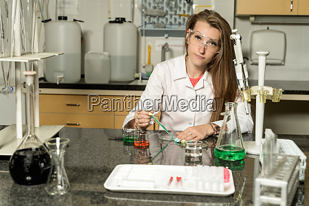 young female laboratory technician sampling with