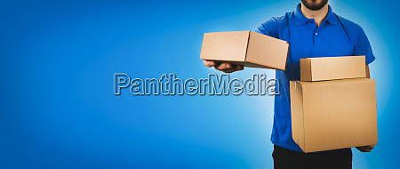 delivery service man holding cardboard boxes