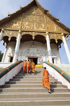 buddhist monks climbing stairs to a