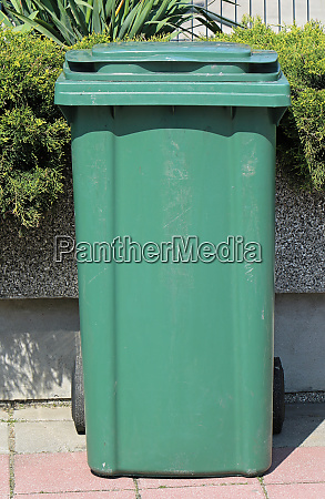 green plastic trash can