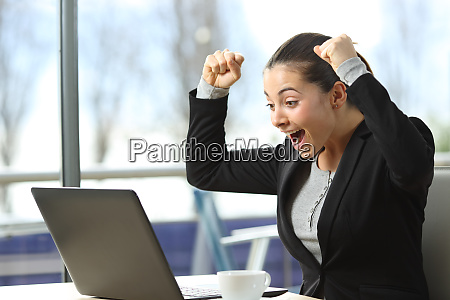 excited businesswoman checking laptop content