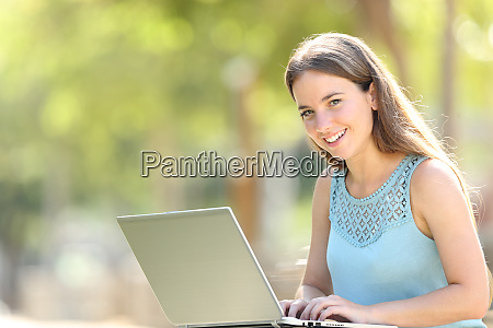 happy woman with a laptop looks