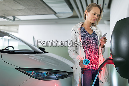 young woman charging an electric vehicle