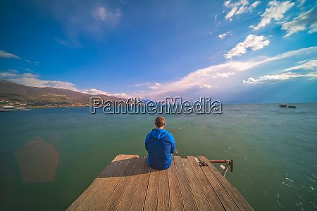 traveller sitting on a wooden pier