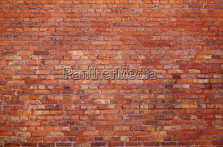 old brick wall with red building