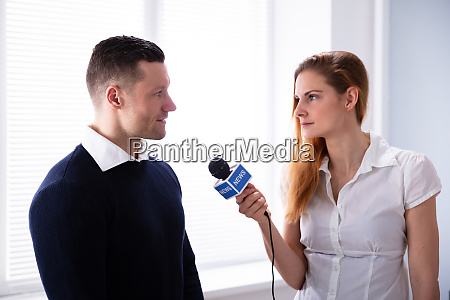 news reporter asking question to businessman