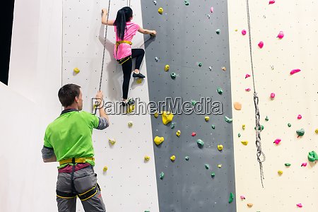 woman getting training of wall climbing