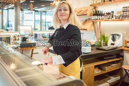 shop clerk in deli cutting cheese