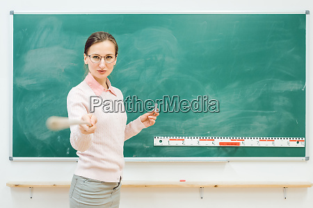 strict teacher pointing with pointer in