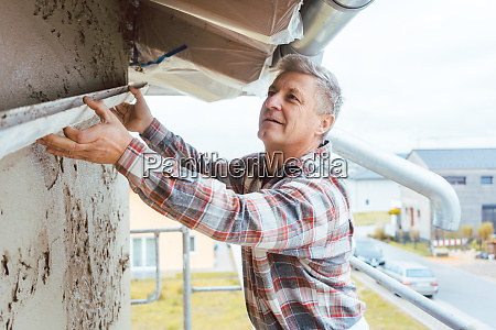 plasterer smoothing plaster on a facade